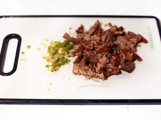 陕西小吃—肉夹馍,将酱好的牛肉切小块,将配菜青椒、青蒜切小丁混合后倒入一些酱牛肉的汤搅匀馅料。