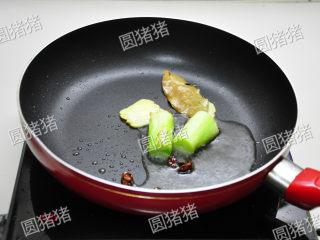 山楂烧排骨,炒锅热油,放入葱段、香叶、八角煎炒出香味。