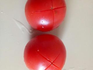 西红柿炖牛肉,西红柿两个洗净,在顶部轻轻的画上十字。