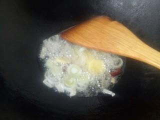 西红柿炖牛肉,再倒入葱花和姜片煸香。