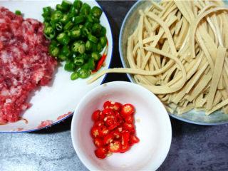 肉末烧豆腐皮,将猪肉剁成肉糜,青红椒洗净切细,豆腐皮切丝。姜蒜剁成末。