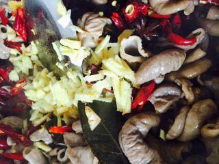 自制香辣干煸肥肠,下干辣椒、姜丝、花椒、泡姜和泡青菜炒出香味后连同肥肠和香料一起下锅炒一会儿