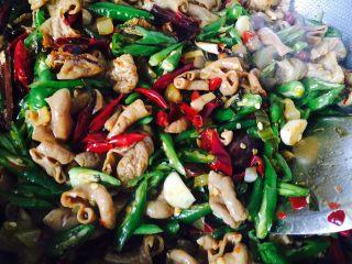 自制香辣干煸肥肠,加入生抽和老抽翻炒,起锅时加鸡精和葱花即可