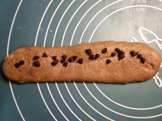 巧克力双色吐司面包,白面团直接卷成长条棍状。巧克力面团铺上巧克力豆,慢慢卷起。