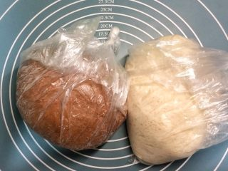 巧克力双色吐司面包,分别揉好两个面团:黄油酵母除外,揉成光滑面团,加入黄油和酵母,揉至完全。用保鲜袋分别装好两个面团,挤出空气,在袋口处打好结,放冰箱里冷藏不低于4摄氏度发酵一晚上(我发了12小时)。