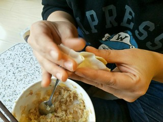 酸菜馅饺子,放入我这个小勺子一勺的馅儿,我个人很粗暴的两手使劲一捏边缘的饺皮就完事了。