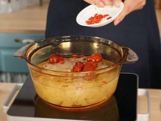 木瓜银耳莲子羹,向锅中倒入纯净水、莲子、枸杞、红枣其他一起煮10分钟。最后待银耳熬出胶质之后加入冰糖调味,把银耳羹倒入木瓜盅里即可。