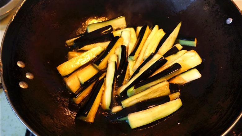 肉末烧茄子,把腌制好的茄子用手挤掉多余水分,油温升高以后下茄子炸,重点来了,记住一定要油温很高了茄子下锅,不然茄子容易变色。炸约不到一分钟,自己观察,变软即可捞起来,不然太软了不好吃。