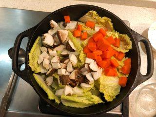 铸铁锅焖蔬菜排骨,加胡萝卜和冬菇丁炒匀。