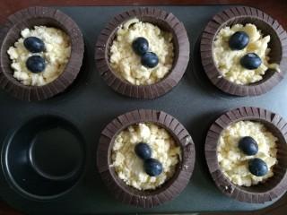 蓝莓酸奶酥粒麦芬,把之前准备好的酥粒均匀撒在上面,全部用完~再每个上面放两粒蓝莓~烤出来会很好看~按压一下,不然烤的时候会掉落~