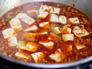 麻婆豆腐,放入豆腐,不要用铲子铲,轻轻晃动锅子,让豆腐均匀裹上汤汁。煮2,3分钟,让豆腐更入味