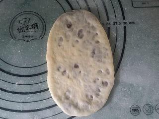 豆沙花瓣面包,用手轻轻按扁、再用擀面仗擀成椭圆形