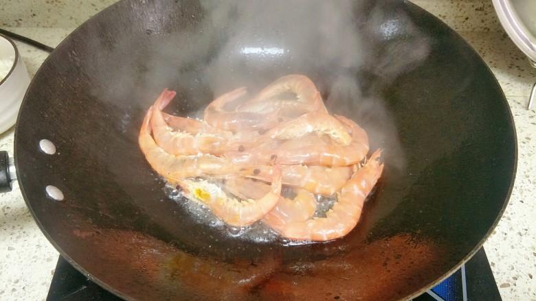 避风塘炒虾,下入明虾大火翻炒,因为油比较多,半炸至酥脆捞出