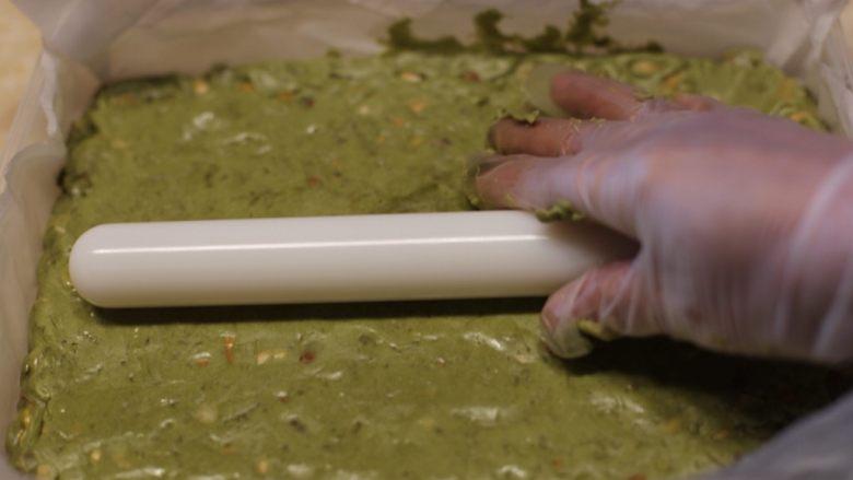 抹茶坚果牛扎,将抹茶坚果糖倒入事先备好的模具中,用擀面杖擀平后放入冰箱冷藏30分钟。