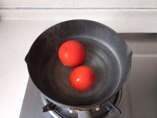 茄汁蓮藕雞肉丸子(親子版)-輔食,番茄洗凈,底部用刀劃十字,小鍋燒開水,放入番茄汆燙一會兒