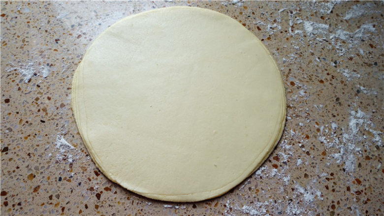春饼,8张面皮全部叠在一起,然后用手轻轻按一下,两面都按,这样一会好擀一些,而且两面轻轻按压也可以调整饼大小均匀度.