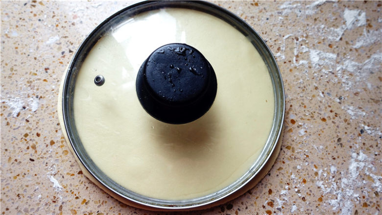 春饼,用洗干净的锅盖,放在面皮上,使劲一压。
