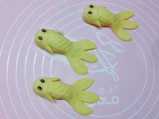 卡通小金鱼,用红豆粘在眼框上做眼睛,再在鱼的两侧剪出鱼鳍,如上图。