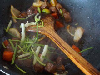 果味牛肉粒,加入葱段炒匀