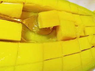快手芒果酥~蛋挞皮版,用勺子很容易就取出芒果肉了,把取出的芒果肉放在合适的容器里