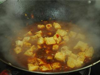 红烧豆腐,烧开后放入豆腐、大火烧煮一分钟,为了避免糊锅,中间适度旋转锅身,取一半水淀粉勾芡,继续旋动锅身烧煮大约一分钟,再放剩下的水淀粉,