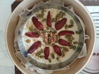 吉祥如意年年糕,最后铺上剩余的米粉,点缀上大枣,坚果,继续蒸18分钟