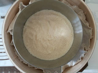 吉祥如意年年糕,铺上一层米粉,刮平,蒸锅中放入水烧开,上锅蒸5分钟