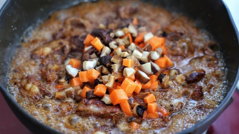 排骨焖饭,倒入热水和排骨持平,改中小火炖煮约半个小时,待锅内剩少许汤汁时加入香菇和胡萝卜翻炒均匀