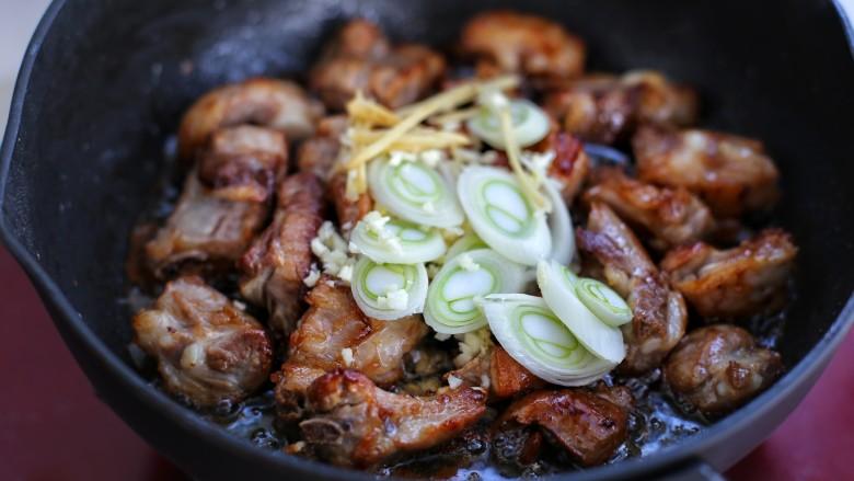 排骨焖饭,接着放入葱花、蒜末和姜丝翻炒均匀
