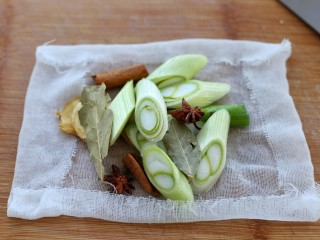 猪皮冻,准备姜片、葱段、香叶、桂皮和八角放到干净的纱布上,包起来做成料包