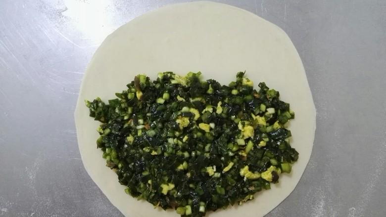 鸡蛋韭菜盒,取出一个面剂,擀成薄的圆面片,将适量的韭菜馅铺在面片的一侧,轻轻地掀起另一侧面皮盖在韭菜馅上,从现在开始每一个动作都要加快,防止韭菜出汁水。