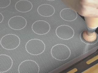 超详细马卡龙教程,将面糊挤在硅胶垫的圆圈内;