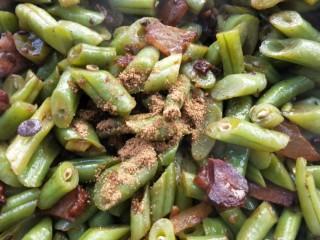四季发财豉香四季豆炒腊肉丁,加五香粉适量,继续煸炒,至四季豆水分慢慢煸炒干。