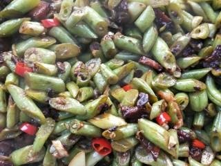 四季发财豉香四季豆炒腊肉丁,加适量盐,鸡精调味,翻炒均匀,即可盛盘。