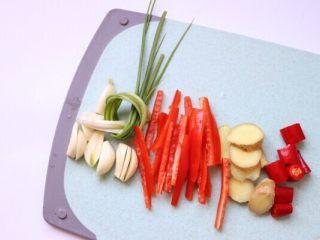 清蒸鲳鱼,葱打结,红椒切丝、蒜瓣和姜切片,红尖椒切段