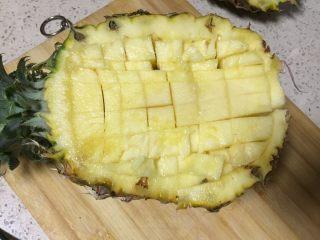 果味糯米凤梨(菠萝)饭,取多的一边周围划先用刀切一圈,再划成粒