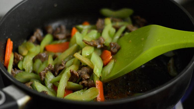 西芹炒牛肉,炒至断生后调入酱油,翻炒均与