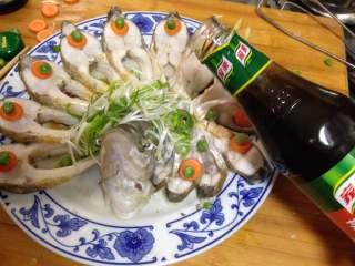 年味——宴客大菜孔雀开屏鱼, 鱼出锅后,倒掉盘子中蒸出的水,摆上泡好的葱丝,用青豆做装饰倒上蒸鱼豉油