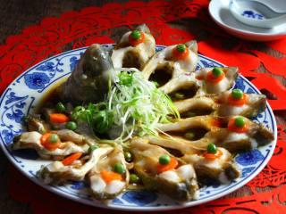 年味——宴客大菜孔雀开屏鱼,将热油均匀交在鱼身上即可上桌。