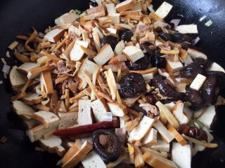 海鲜卤面,随后先放入香干片煸炒,把香干的豆腥味煸炒出去,然后放入香菇、干花菜、笋干,煸炒片刻。