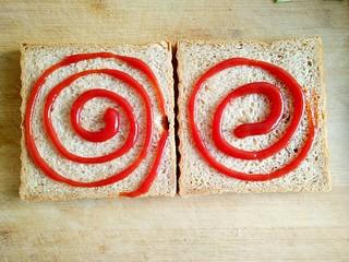 沼三明治,在吐司片上涂抹适量的番茄酱。