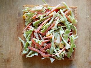 沼三明治,在涂抹好番茄酱的吐司片上均匀铺上一层卷心菜沙拉。