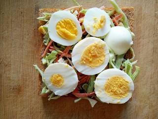 沼三明治,在卷心菜沙拉上铺上鸡蛋片。