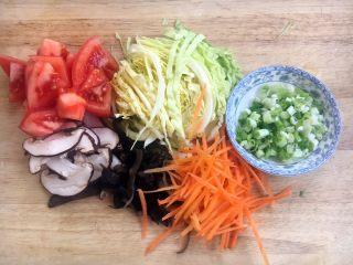 天津特色小吃 蔬菜烩饼,将圆白菜切丝,胡萝卜切丝,木耳切丝,香菇切丝,西红柿切块,小香葱切成葱花。