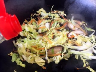 天津特色小吃 蔬菜烩饼,倒入1勺的酱油,翻炒均匀。