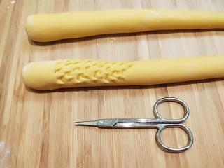 二龍戏珠南瓜面点,在用小剪刀剪龙鳞片。