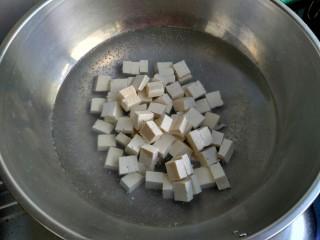 麻婆豆腐,起锅烧水,水开把豆腐放入煮一分钟。用开水焯豆腐可以去除豆腥味,也可以保持豆腐形状不易碎。