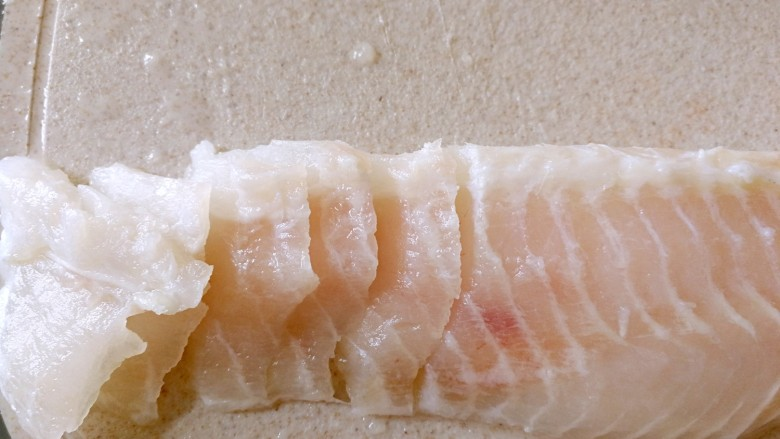 番茄豆腐巴沙鱼~让孩子爱上吃饭,巴沙鱼一切为二,逆着纹路,刀倾斜45度切片