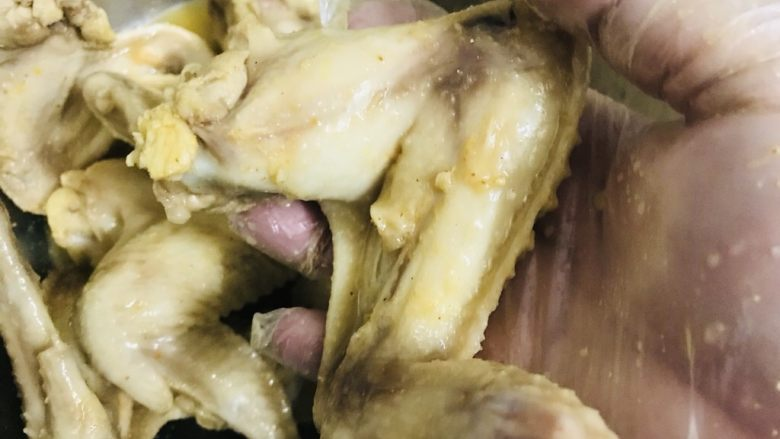 盐焗鸡翅(家常版),戴手套把腌料抓均匀,放入冰箱包保鲜膜腌一晚上。