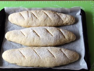 粗粮长棍面包,把长棍面团移入烤盘纸上,发酵帆布很好用,轻轻拿出一点不粘,再用美工刀划几刀,筛上面粉。